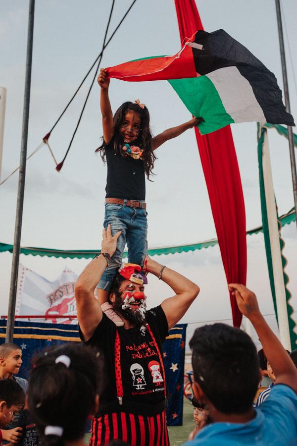 Niña ondeando la bandera palestina en brazos de Iván Prado